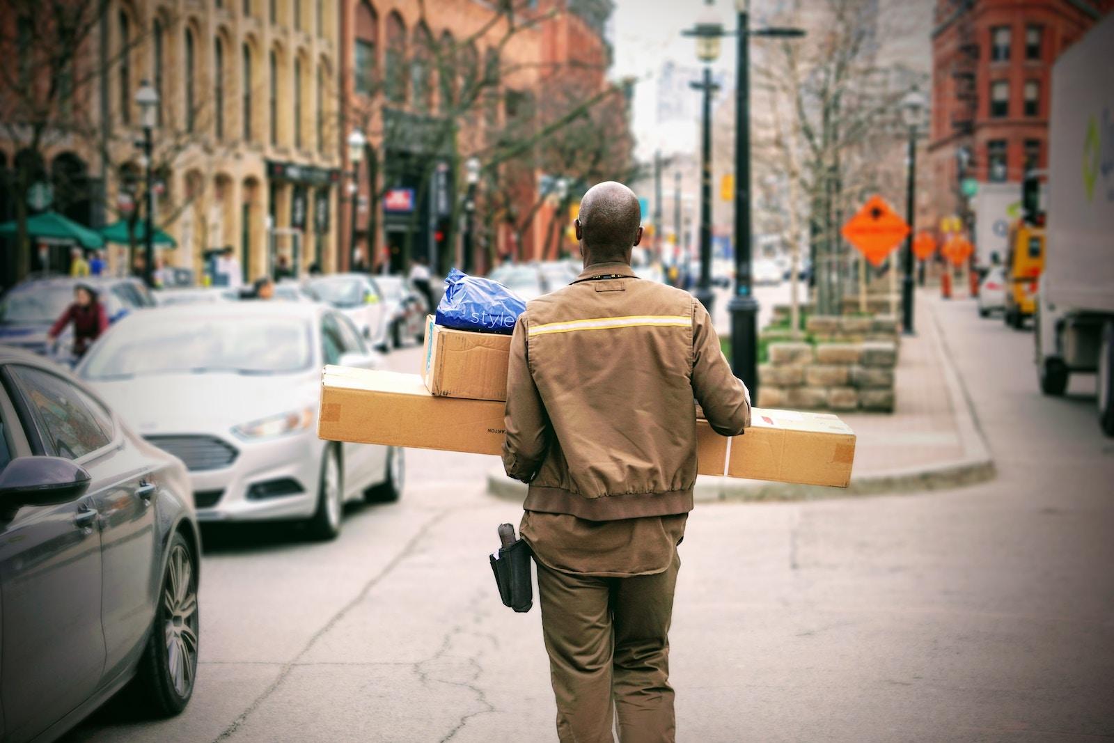 kurier niosący paczki po ulicy w mieście.